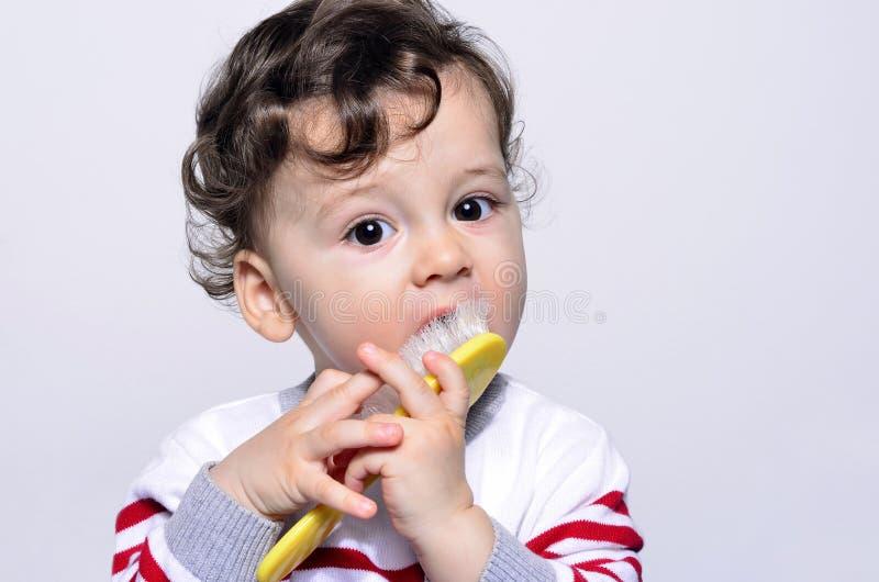 设法一个逗人喜爱的卷发的婴孩的画象梳他的头发 免版税库存照片