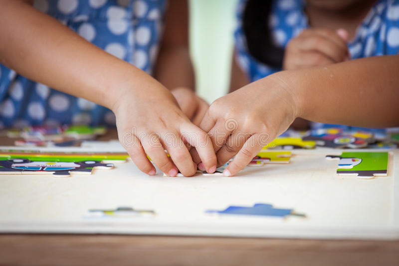 设法两只儿童的手帮助和连接七巧板 库存照片