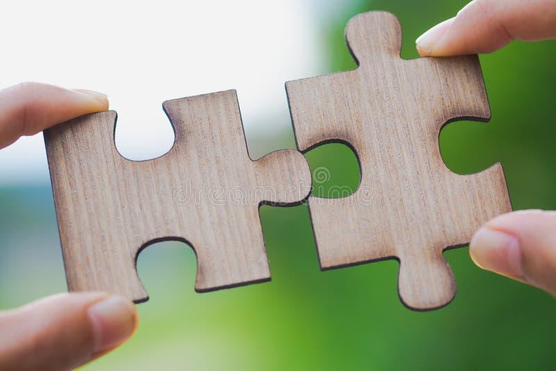 设法两只的手连接夫妇困惑与绿色backg的片断 图库摄影
