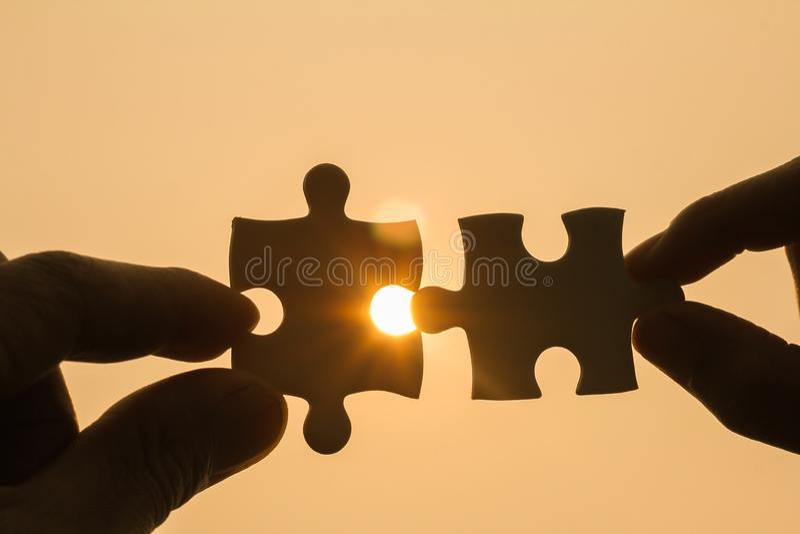 设法两只的手连接夫妇困惑片断有日落背景 协会和连接的标志 免版税库存照片