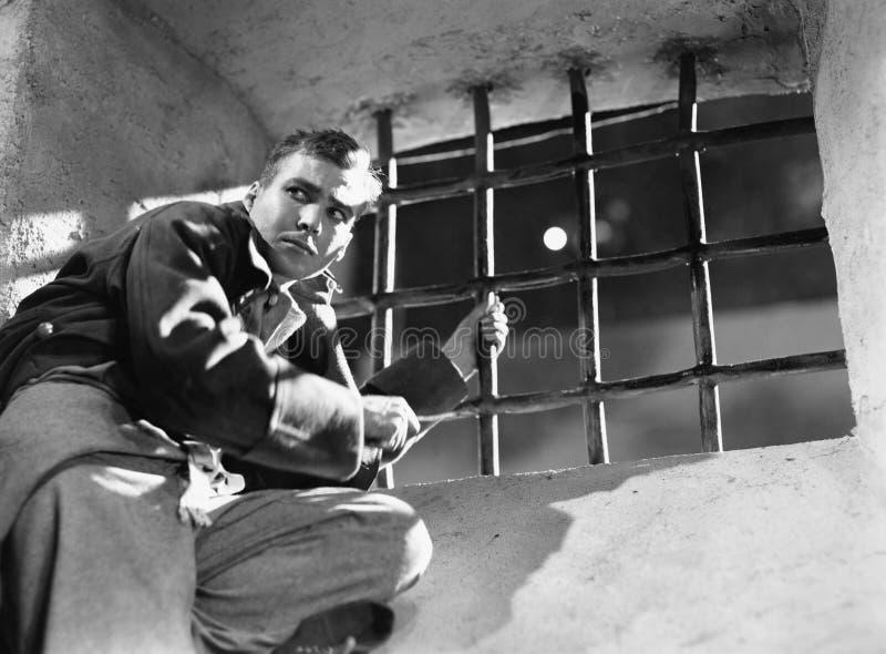 设法低角度观点的一个年轻的人从监狱牢房逃脱(所有人被描述不更长生存,并且庄园不存在 库存照片
