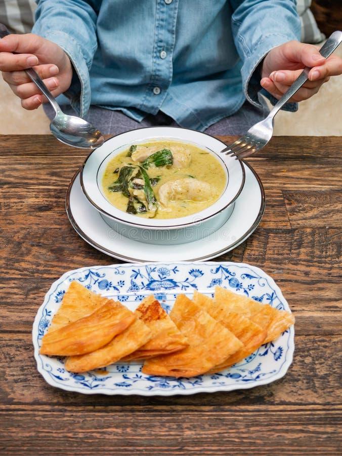 设法使用叉子和匙子吃膳食 种类印度食物由面粉,与绿色咖喱鸡的Roti制成在白色板材 库存图片