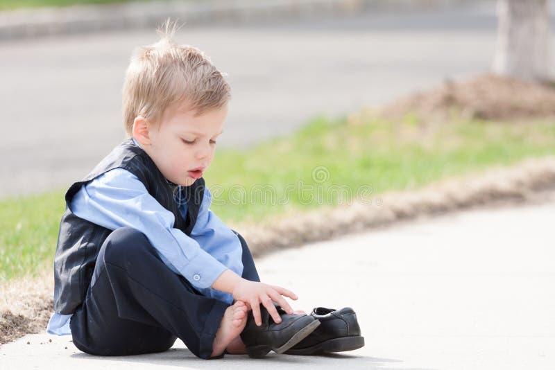 设法可爱的小孩的男孩投入他的鞋子  免版税库存图片