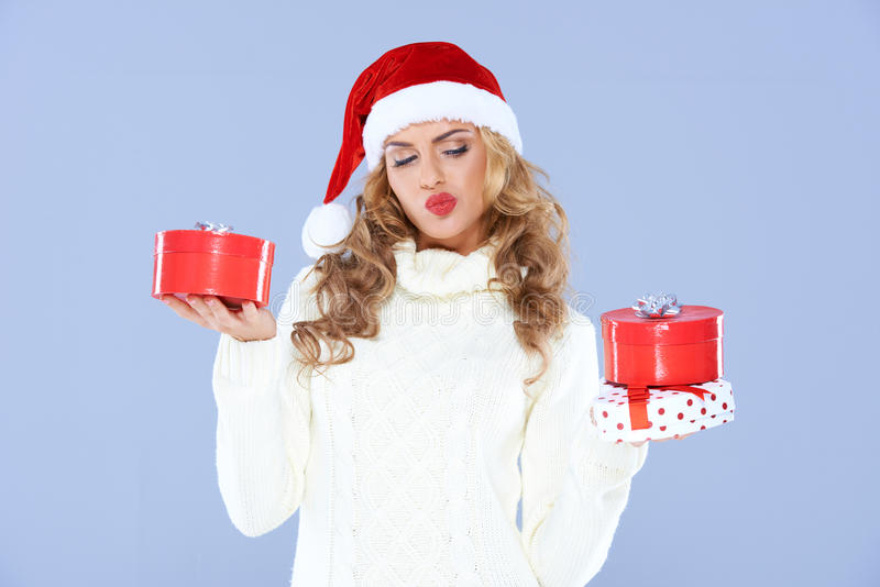 设法圣诞老人的帽子的性感的妇女决定 免版税库存照片