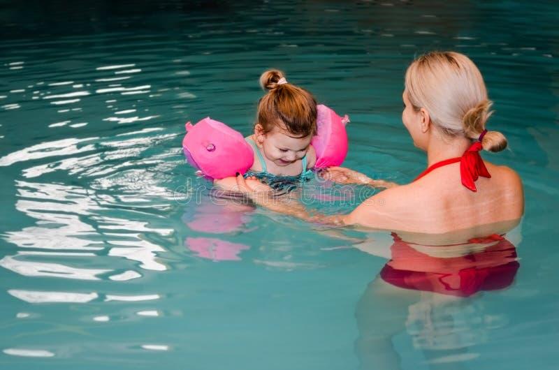 设法年轻的母亲学会游泳在她的水池的小女儿 r 免版税库存照片