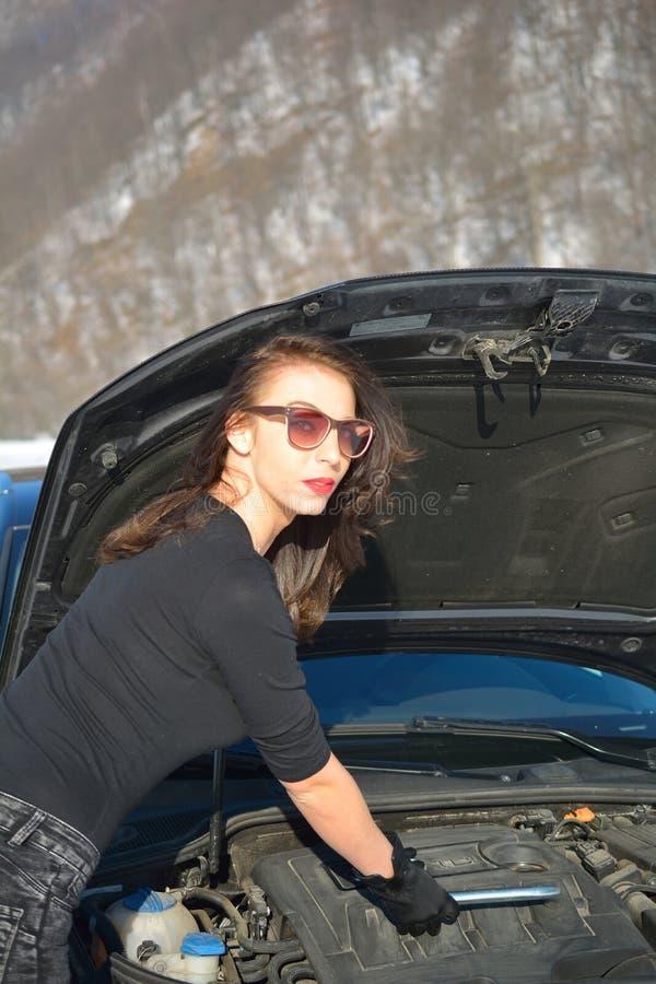 设法年轻的美女修理汽车 库存图片