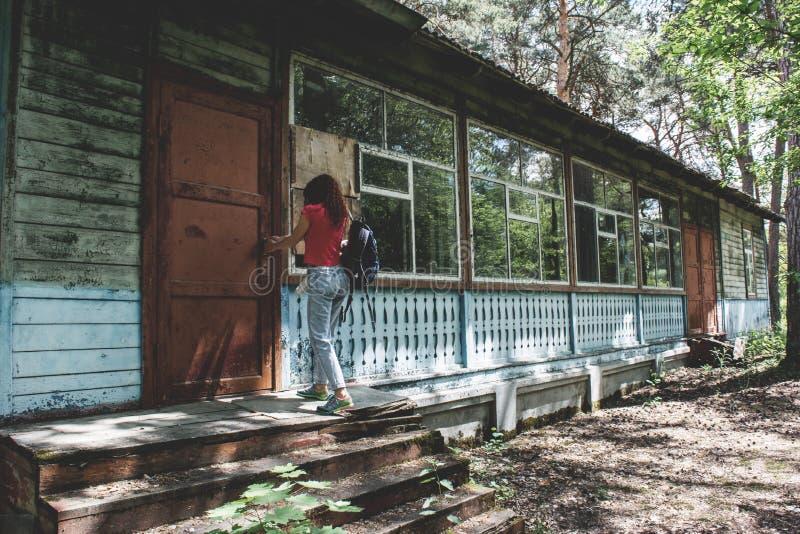 设法年轻美丽的女孩打开被放弃的房子的门 免版税库存图片