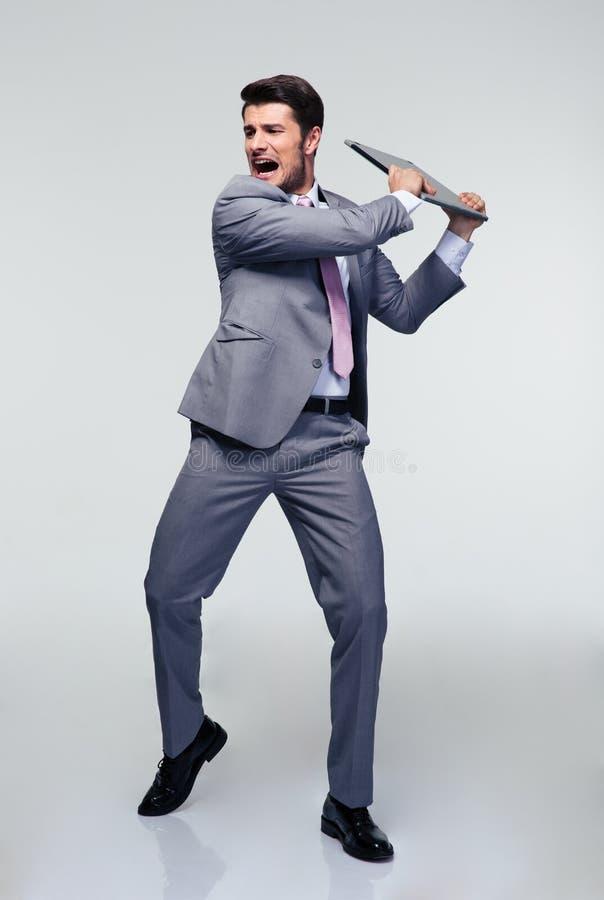 设法恼怒的商人捣毁他的膝上型计算机 免版税图库摄影