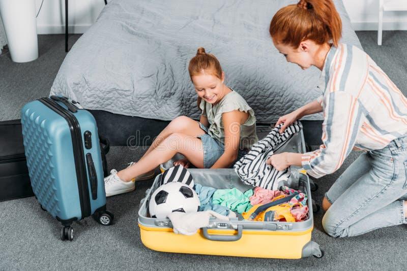设法愉快的母亲包装衣裳入手提箱,当女儿开会时 库存照片