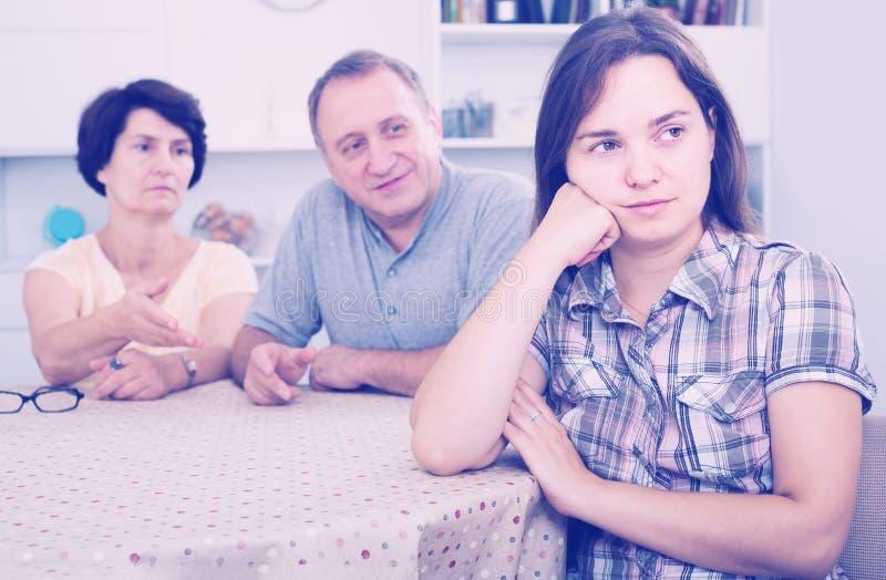 设法成熟的父母听女儿和帮助 库存图片
