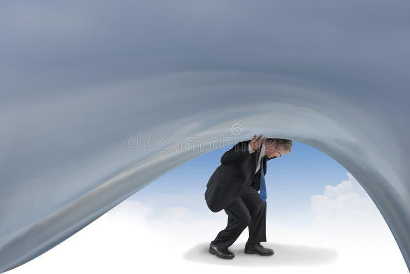 设法沮丧的人拖延包围他的风雨如磐的消沉天空 免版税图库摄影