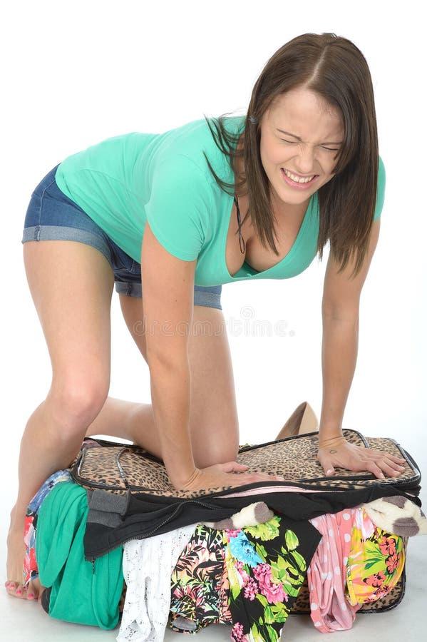 设法沮丧的被注重的恼怒的少妇关闭一个溢出的手提箱 库存图片