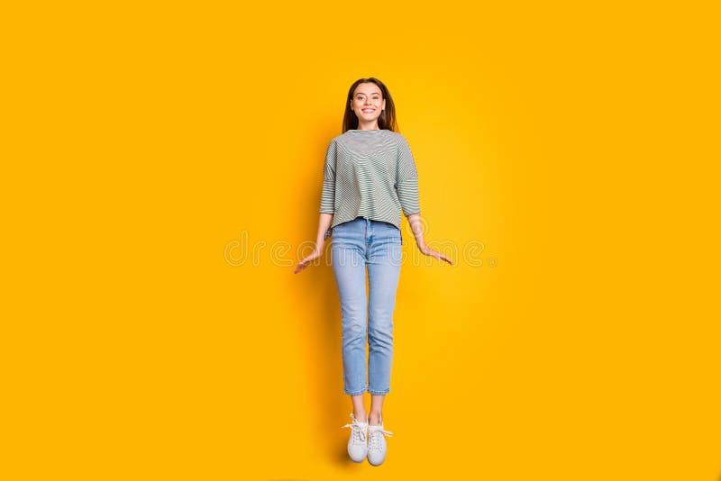 设法浮动女孩全长身体尺寸的照片飞行,不用飞机,当隔绝有黄色背景时 库存照片