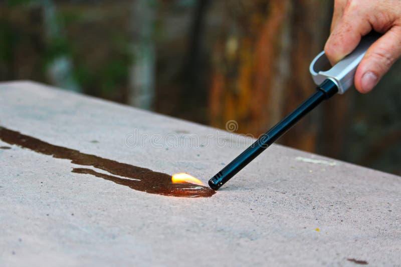 设法点燃在火的流体与丁烷打火机 免版税库存图片