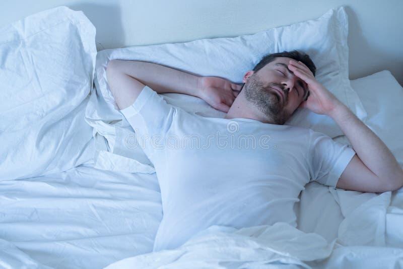设法生气的人睡觉在他的床上在晚上 免版税库存照片