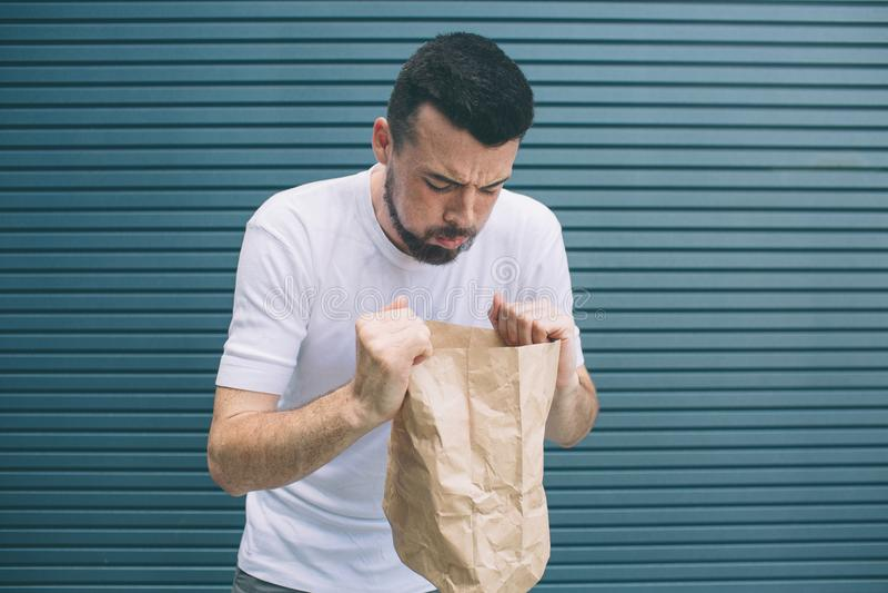 设法病的人的图片呕吐在纸袋 他感到可怕 隔绝在镶边和蓝色背景 免版税库存照片