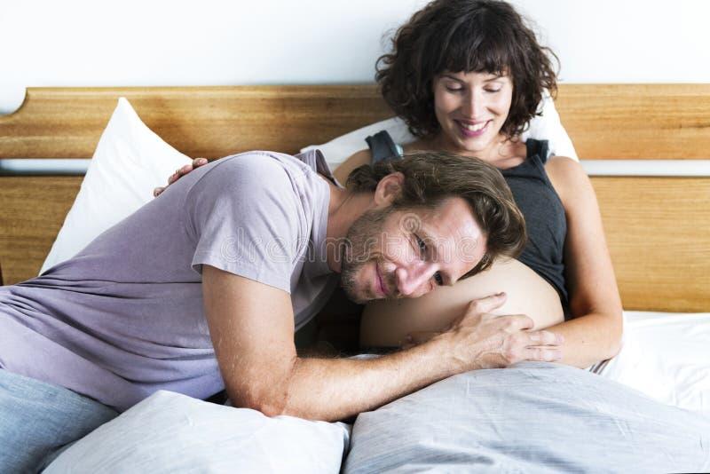 设法的丈夫听见腹部的婴孩 免版税库存照片