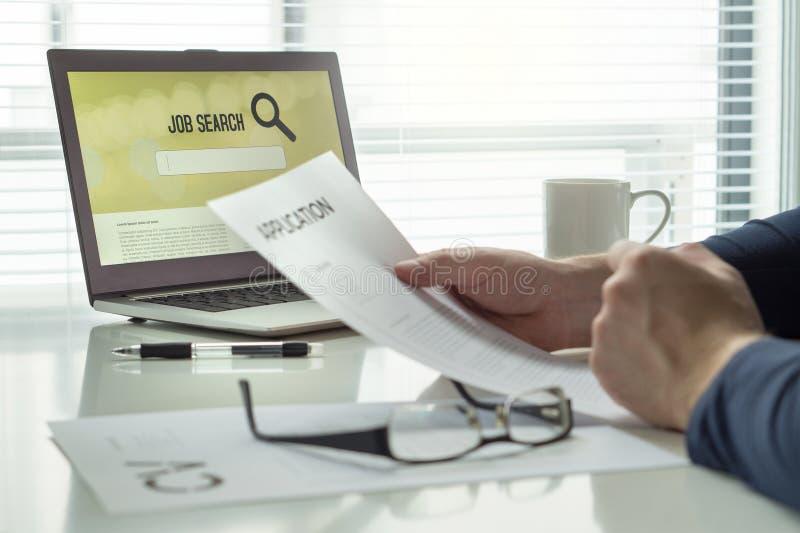 设法的人读他的工作申请书纸和cv或者履历和发现工作和得到聘用 求职者在家庭办公室 库存照片