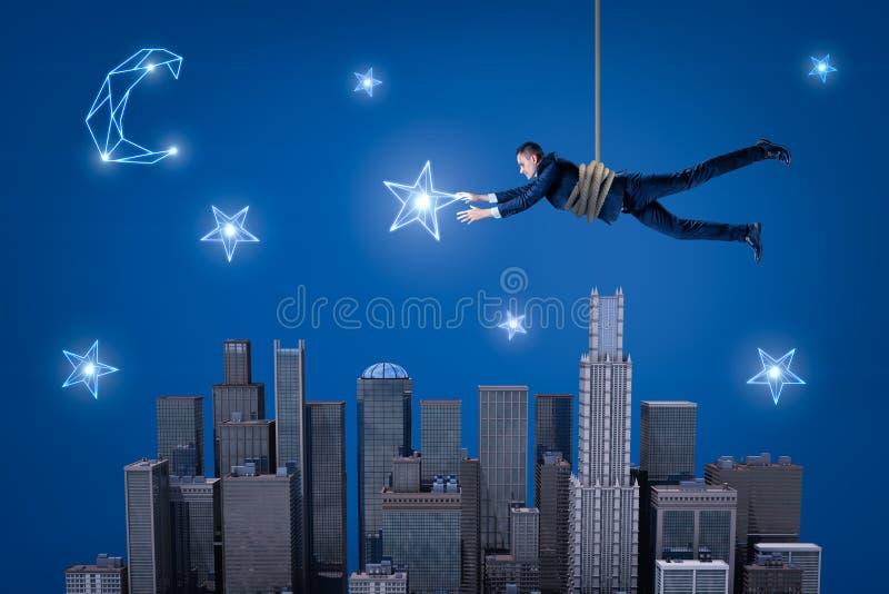 设法的商人垂悬在夜城市上的一条绳索和捉住在天空的一个星 向量例证