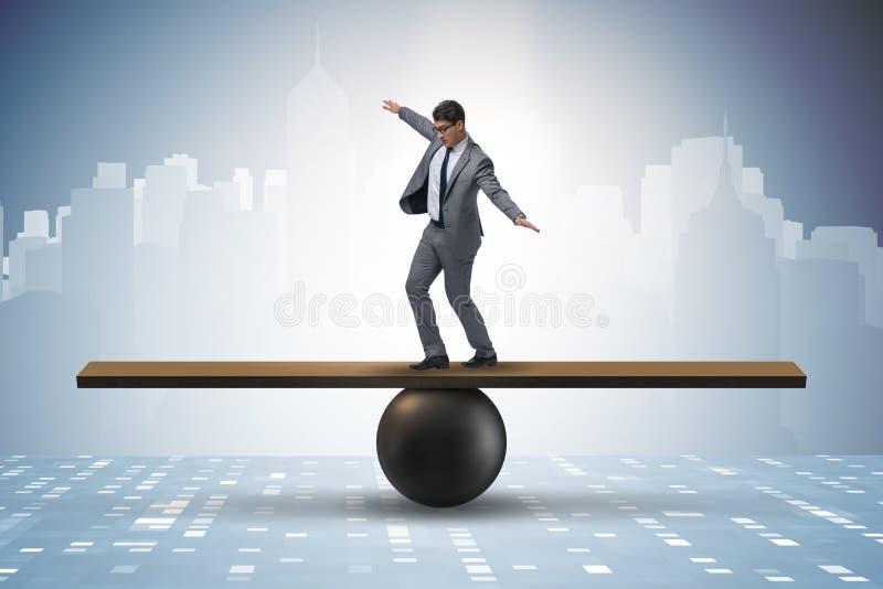 设法的商人平衡在球和跷跷板 免版税图库摄影