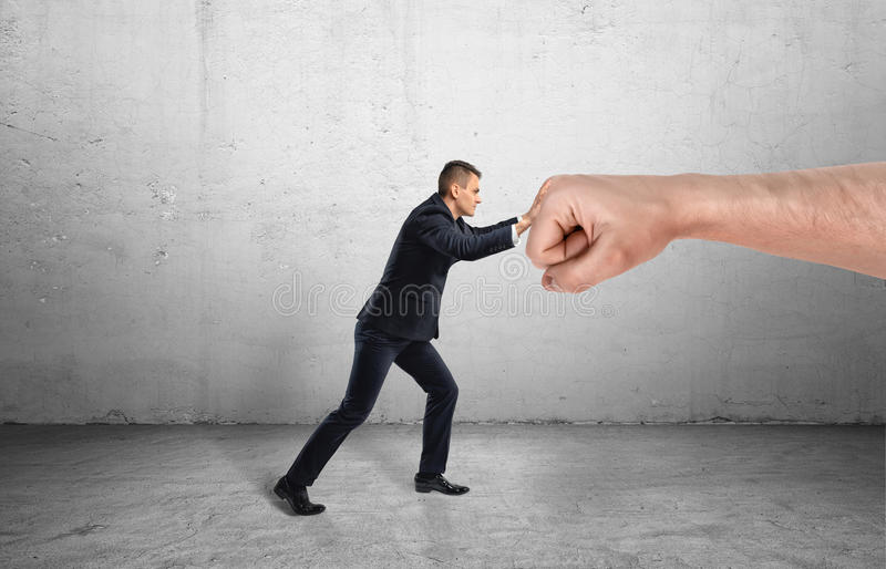 设法的商人抵抗巨大的男性拳头和移动它在灰色背景 免版税库存照片