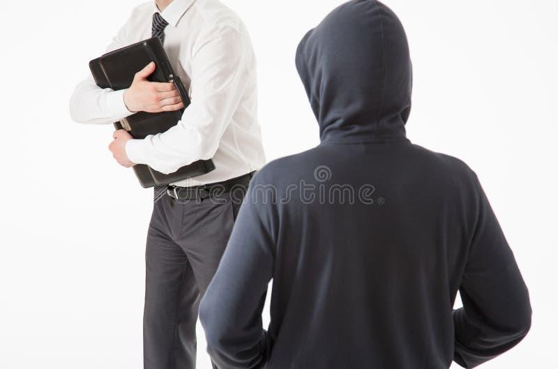 设法的商人由未知的人掩藏他的公文包 免版税库存照片