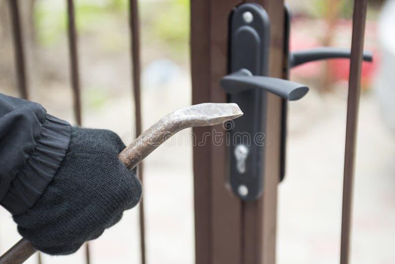 设法的夜贼打破有撬杠的门 使用撬杠,设法的夜贼强迫锁 免版税库存图片