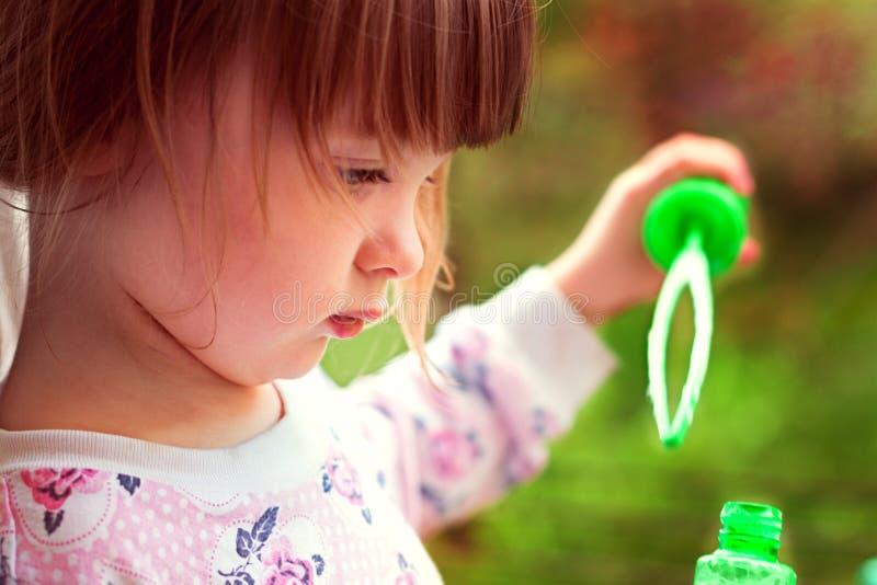 设法的女孩吹肥皂泡 免版税库存图片