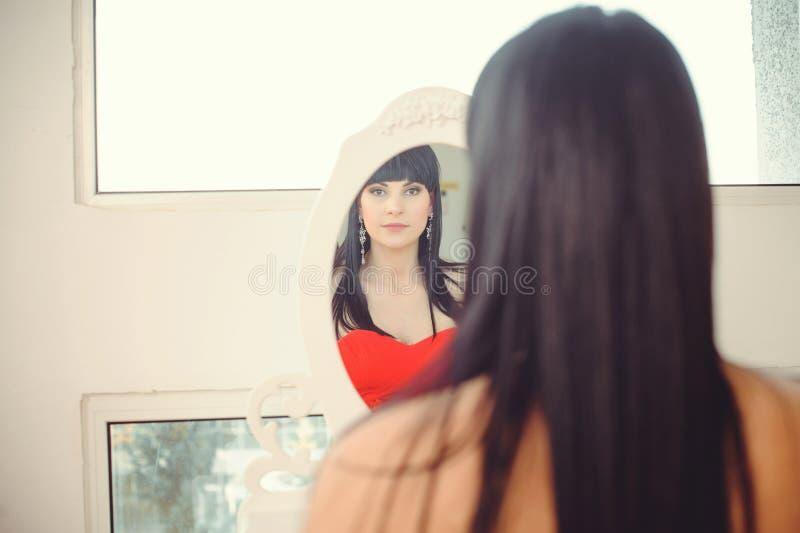 设法的女孩穿戴看在镜子,快乐和愉快 逗人喜爱的美丽的混合的族种亚洲人/白种人年轻女人红色的 免版税库存图片