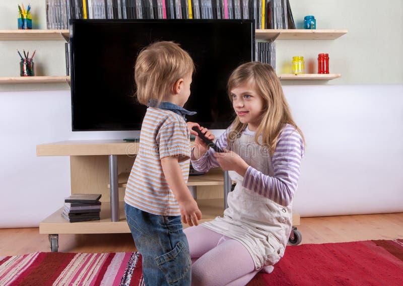 设法的女孩从她的小汤得到遥控 库存照片
