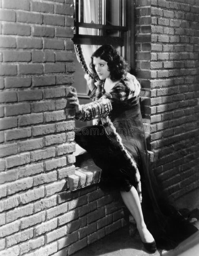 设法的妇女通过窗口逃脱(所有人被描述不更长生存,并且庄园不存在 供应商保单tha 图库摄影