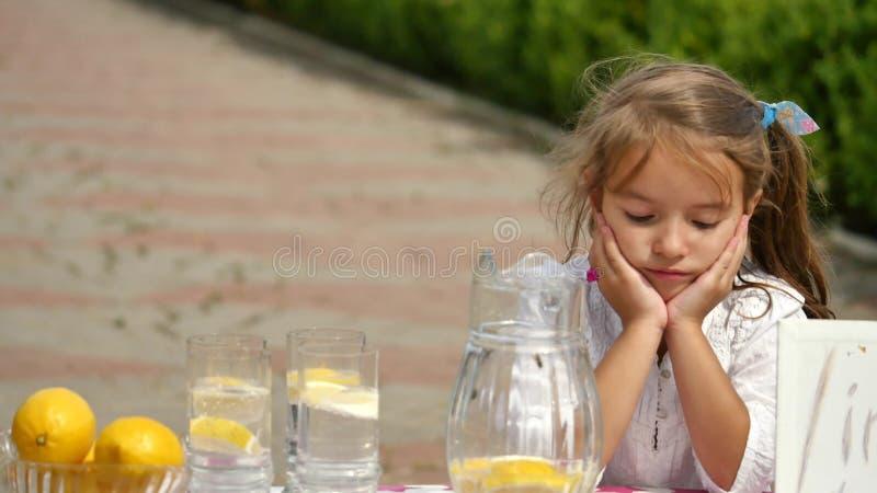 设法的小女孩卖柠檬水 免版税库存图片