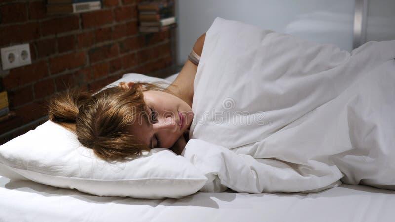 设法的少妇睡觉在床上在晚上 库存图片