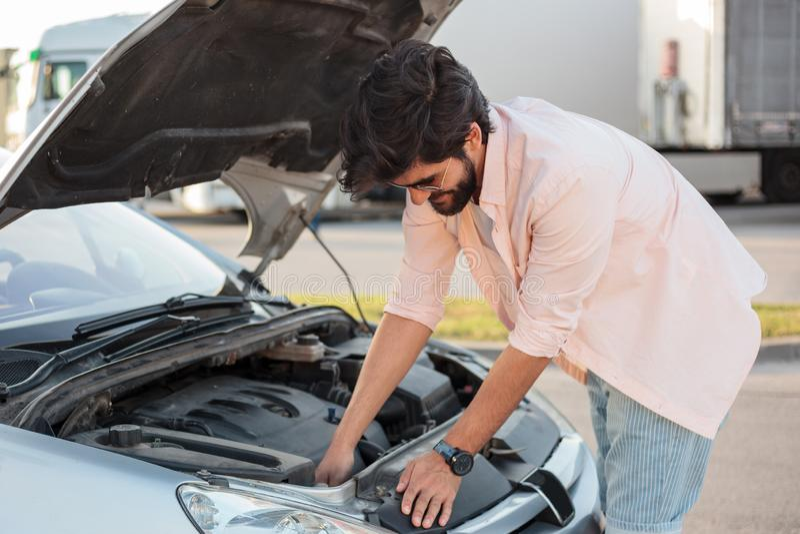 设法的年轻人修理一辆残破的汽车 免版税库存照片