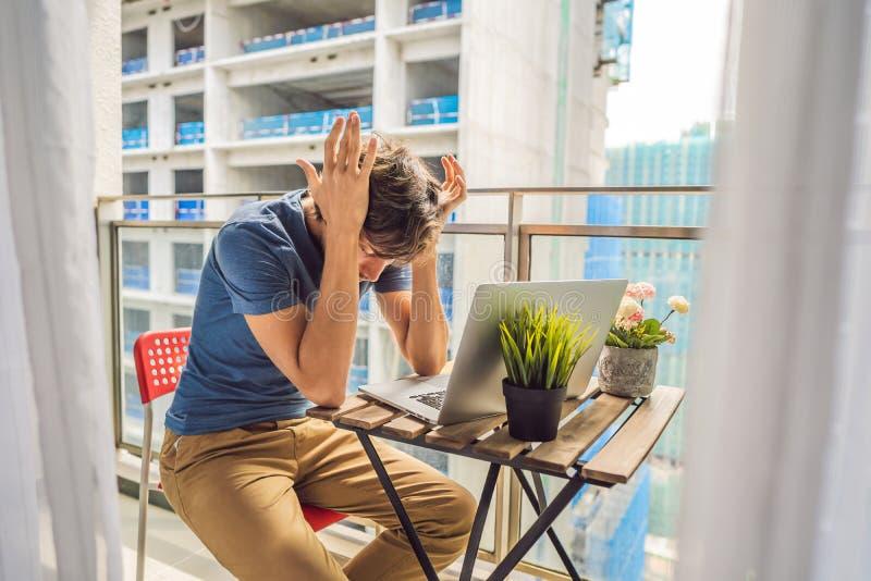 设法的年轻人在大厦工作懊恼的阳台工作外面 噪声概念 空气污染从 免版税库存图片