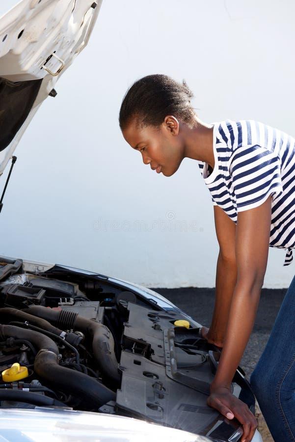 设法的路的年轻黑人妇女修理失败的汽车 免版税库存照片