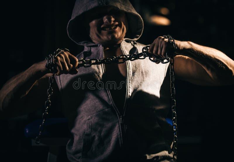 设法积极的爱好健美者的画象撕毁金属链子 免版税图库摄影