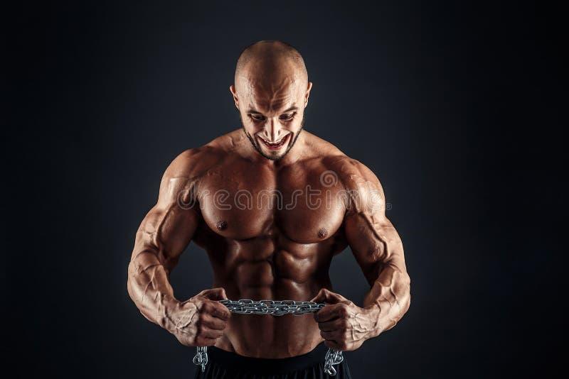 设法积极的爱好健美者的画象撕毁金属链子 图库摄影