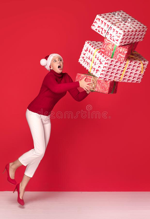 设法红色圣诞老人项目的帽子的妇女拿着堆礼物盒,在红色演播室背景 圣诞节购物,拷贝空间 库存照片