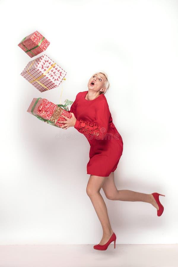 设法红色的礼服的妇女拿着堆礼物盒,在红色演播室背景 圣诞节购物,拷贝空间 免版税库存图片