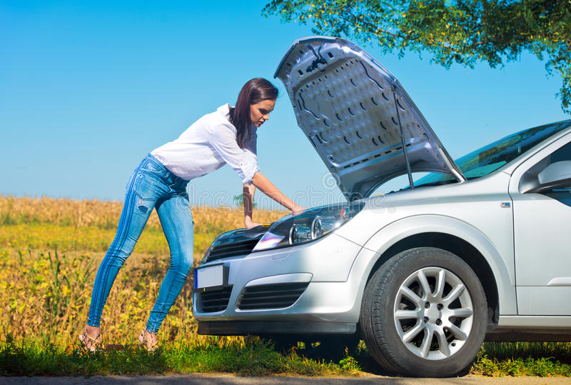 设法美丽的妇女修理一辆残破的汽车 免版税图库摄影