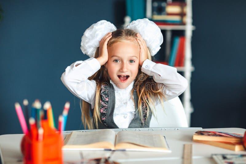 设法美丽的学校的女孩学习有许多家庭作业它驾驶她疯狂在刺激低性能孩子 免版税库存图片