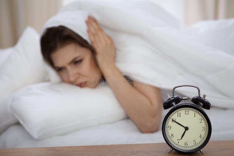 设法美丽的睡觉的妇女在床上和醒与闹钟 有的女孩与早早起来的困难 免版税图库摄影