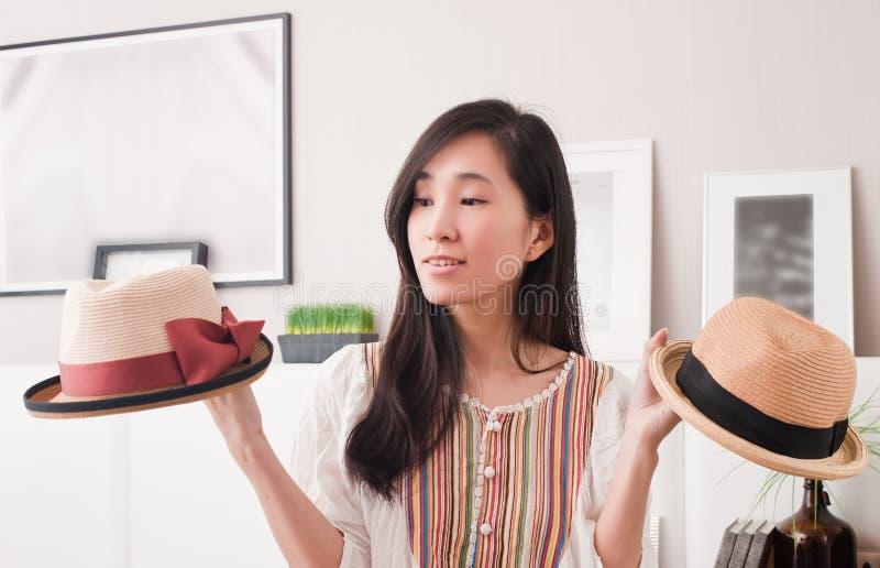 设法迷茫的年轻亚裔的妇女选择时尚帽子在试衣间 免版税库存图片