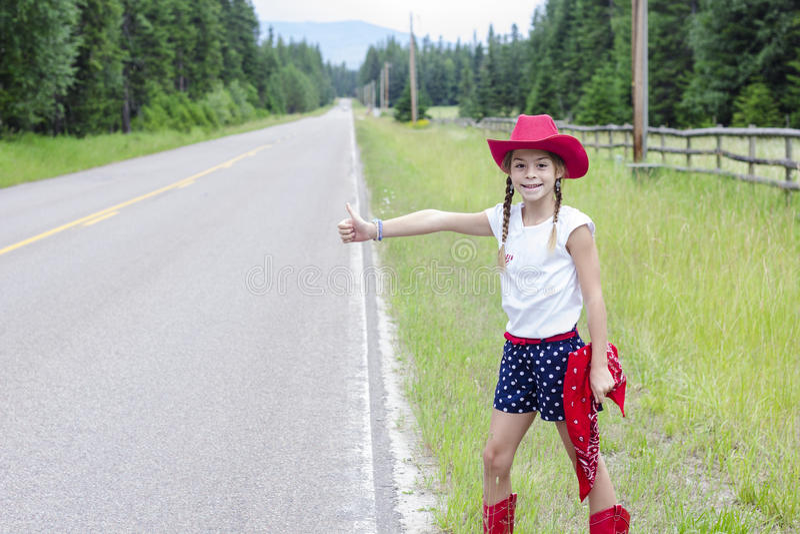 设法逗人喜爱的矮小的女牛仔搭车在一条偏僻的路的乘驾 库存图片