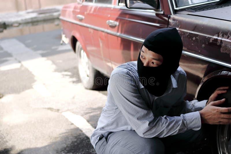 设法黑的巴拉克拉法帽的被掩没的窃贼闯进汽车 犯罪罪行概念 免版税图库摄影