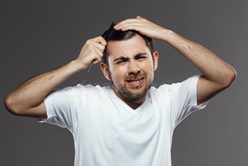 设法年轻英俊的人梳在灰色背景的头发 库存照片
