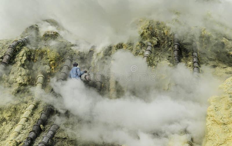 设法Kawah伊真火山的别动队员投入烟,印度尼西亚 图库摄影