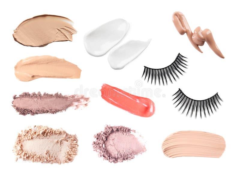 设置与唇膏、眼影、皮肤基础和假睫毛样片在白色背景 图库摄影