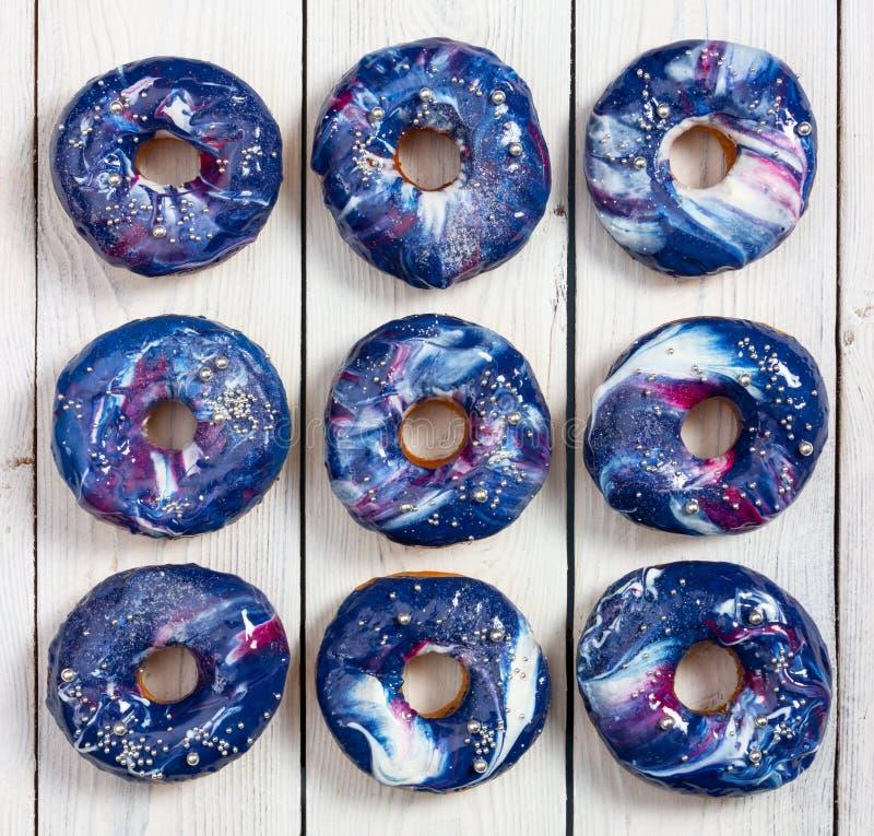 设置与宇宙结冰的油炸圈饼,并且银在木背景洒 免版税图库摄影